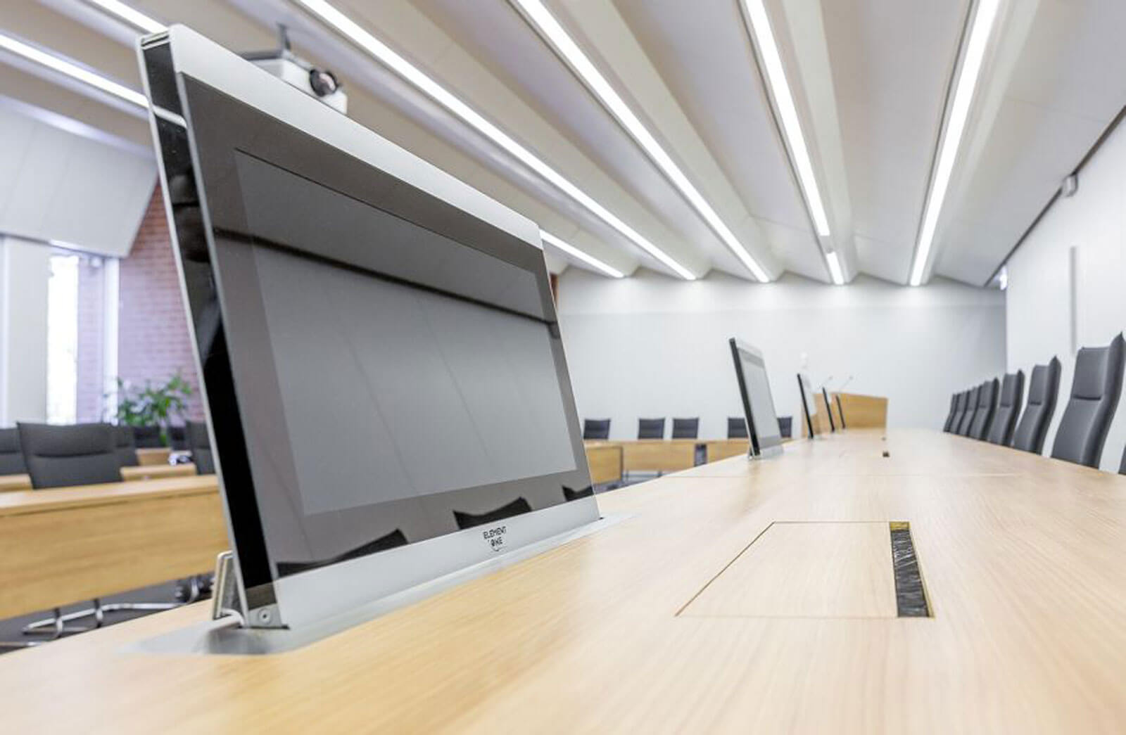 Retractable monitors along long table by ELEMENT ONE